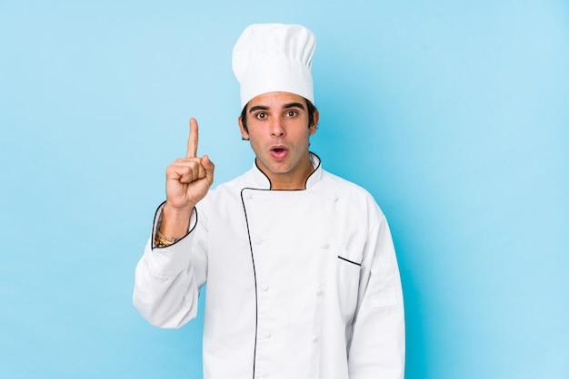 Homme jeune cuisinier isolé ayant une excellente idée, concept de créativité.
