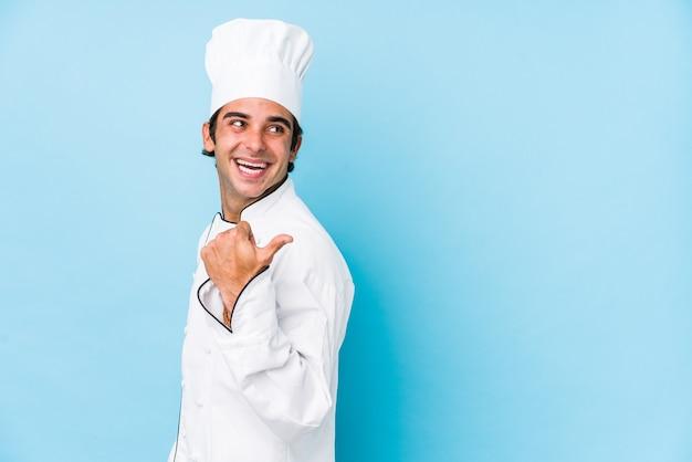 Homme jeune cuisinier isolé des points avec le pouce, riant et insouciant.