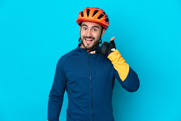 Homme jeune cycliste isolé sur mur bleu faisant le geste du téléphone. rappelez-moi signe