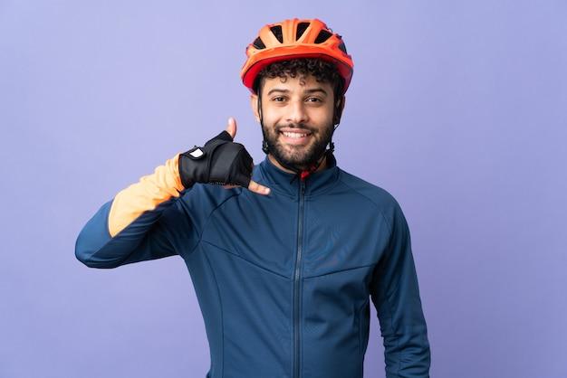 Homme jeune cycliste marocain isolé sur mur violet faisant un geste de téléphone. rappelez-moi signe