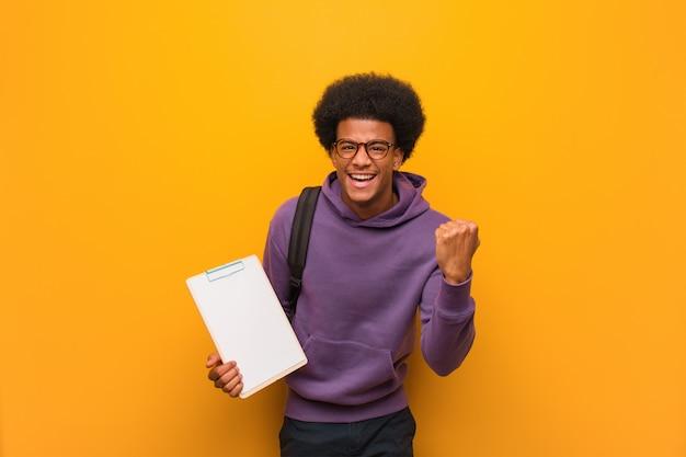 Homme jeune étudiant afro-américain tenant un presse-papiers surpris et choqué