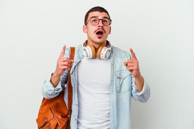 Homme jeune étudiant caucasien, écouter de la musique sur blanc pointant vers le haut avec la bouche ouverte.