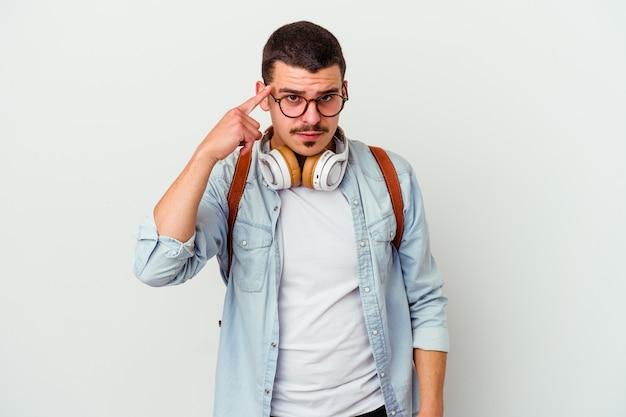 Homme jeune étudiant caucasien, écouter de la musique isolée sur un mur blanc pointant le temple avec le doigt, pensant, concentré sur une tâche.