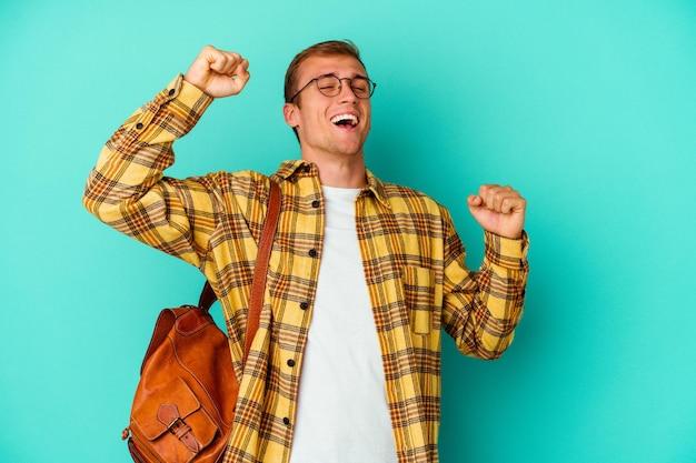 Homme jeune étudiant caucasien isolé sur bleu célébrant une journée spéciale, saute et lève les bras avec énergie.