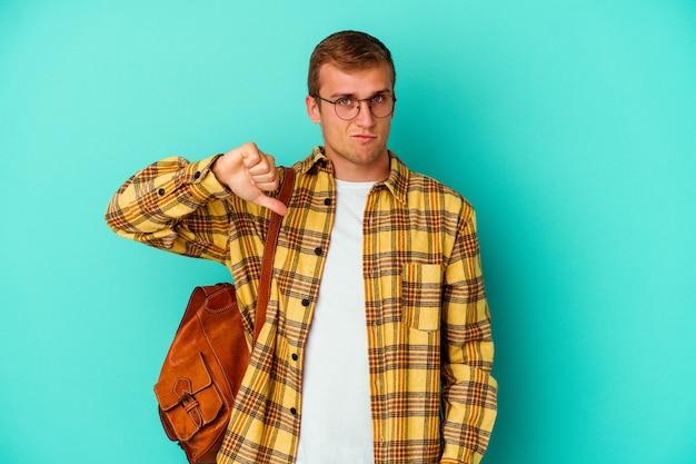 Homme jeune étudiant caucasien isolé sur un mur bleu montrant un geste de dégoût, les pouces vers le bas. concept de désaccord.