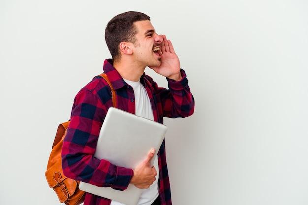 Homme jeune étudiant caucasien tenant un ordinateur portable sur blanc criant et tenant la paume près de la bouche ouverte.