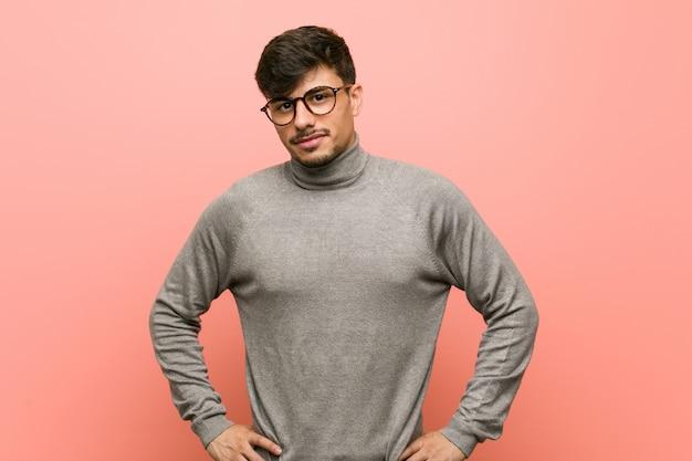 Homme jeune étudiant intelligent confiant en gardant les mains sur les hanches.