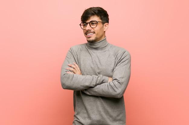Homme jeune étudiant intelligent souriant confiant avec les bras croisés.