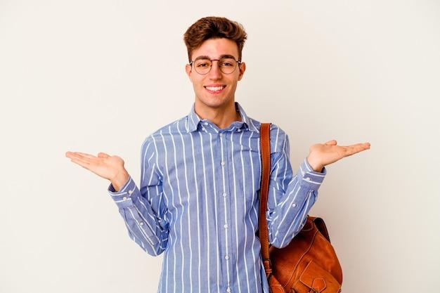 Homme jeune étudiant isolé sur un mur blanc fait échelle avec les bras, se sent heureux et confiant