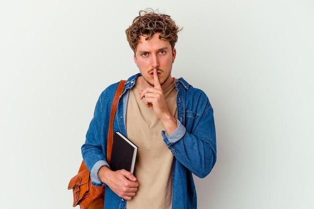 Homme jeune étudiant isolé sur un mur blanc en gardant un secret ou en demandant le silence
