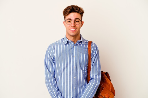 Homme jeune étudiant isolé sur un mur blanc heureux, souriant et joyeux