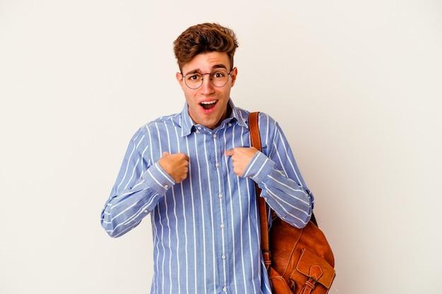 Homme jeune étudiant isolé sur un mur blanc surpris en pointant avec le doigt, souriant largement