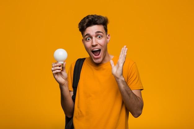 Homme jeune étudiant tenant une ampoule heureuse, souriante et gaie.