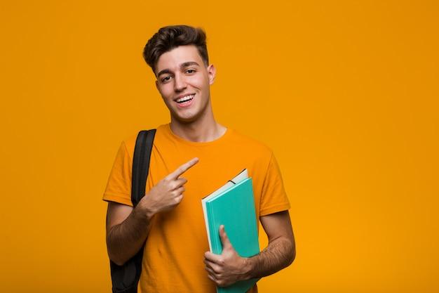 Homme jeune étudiant tenant des livres pointant du doigt vers vous, comme si l'invitation s'approchait.