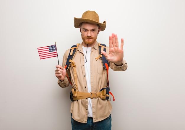 Homme jeune explorateur rousse mettant la main devant. tenant un drapeau des états-unis.
