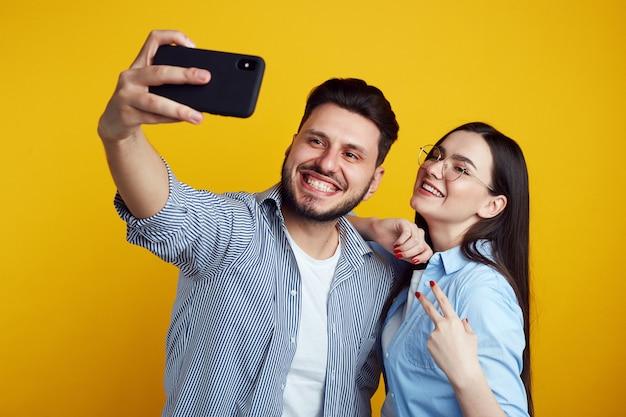 Homme et jeune femme prenant selfie en studio isolé sur mur jaune