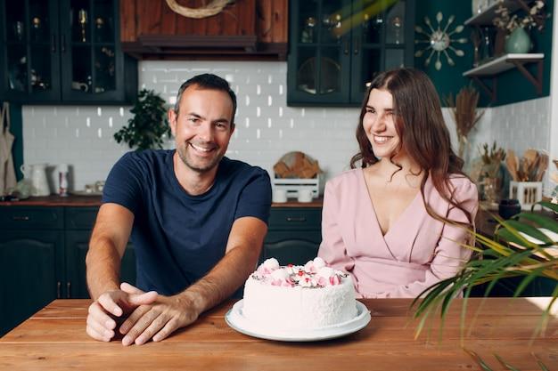 L'homme et la jeune femme sont assis dans la cuisine à domicile avec un gâteau sur la table.