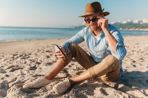 Homme jeune hipster attrayant assis sur la plage au bord de la mer en vacances d'été