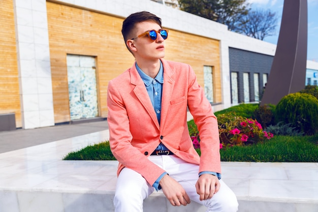 Homme jeune hipster élégant posant dans la rue commerçante