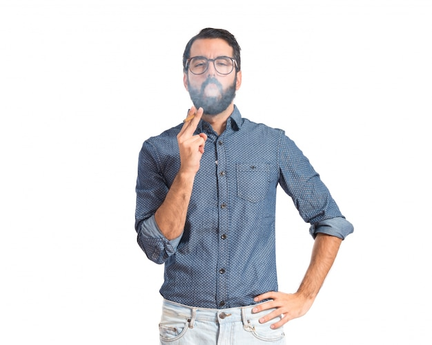 Homme jeune hipster fumant sur fond blanc