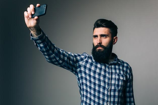 Homme jeune hipster avec une longue barbe prenant selfie avec les mains sur la barbe debout sur un mur gris