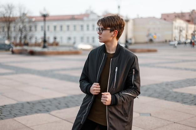 Homme jeune hipster à la mode dans des lunettes élégantes avec une coiffure élégante dans une longue veste noire à la mode dans un t-shirt posant dans la ville à l'extérieur par une chaude journée d'automne. mec cool pour une promenade.
