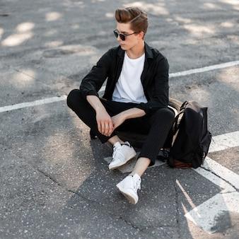 Homme jeune hipster moderne dans des lunettes de soleil sombres dans des vêtements à la mode dans des chaussures blanches