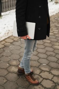 Homme jeune hipster avec ordinateur portable à la main avec un look urbain en ville