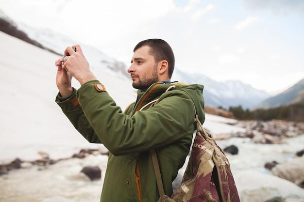 Homme jeune hipster, prendre des photos à l'aide de smartphone, nature sauvage, vacances d'hiver, randonnée