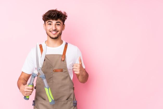 Homme jeune jardinier arabe isolé souriant et levant le pouce vers le haut