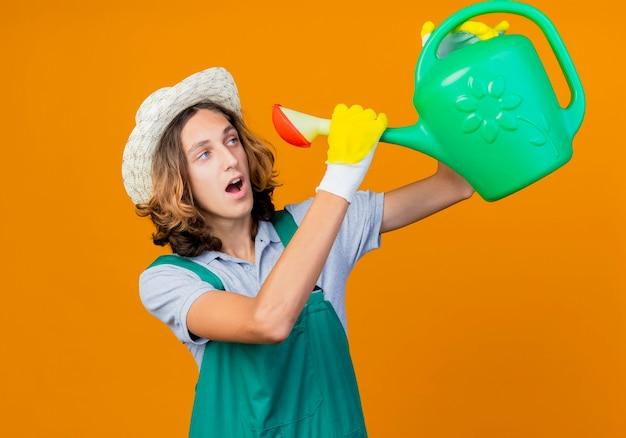 Homme jeune jardinier dans des gants en caoutchouc portant combinaison et chapeau tenant un arrosoir