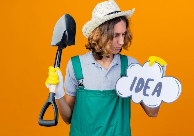 Homme jeune jardinier dans des gants en caoutchouc portant une combinaison tenant une pelle et une bulle de dialogue