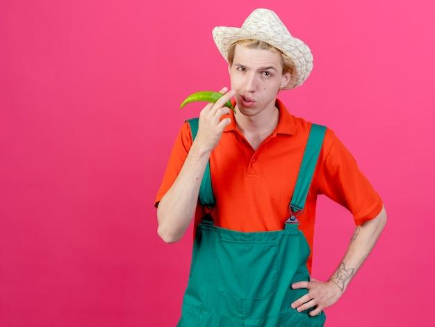 Homme jeune jardinier portant combinaison et chapeau tenant le piment vert comme un cigare