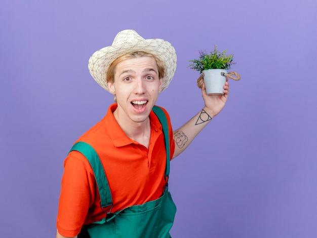 Homme jeune jardinier portant combinaison et chapeau tenant une plante en pot regardant la caméra en souriant avec un visage heureux debout sur fond violet