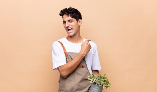 Homme jeune jardinier se sentant heureux, positif et prospère, motivé face à un défi ou célébrant de bons résultats