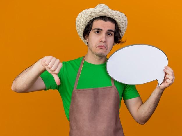 Homme jeune jardinier en tablier et chapeau tenant un signe de bulle de discours vierge montrant les pouces vers le bas avec une expression triste sur le visage debout sur un mur orange