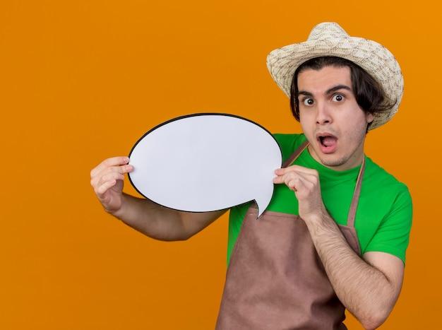 Homme jeune jardinier en tablier et chapeau tenant un signe de bulle de discours vierge regardant la caméra surpris et étonné debout sur fond orange