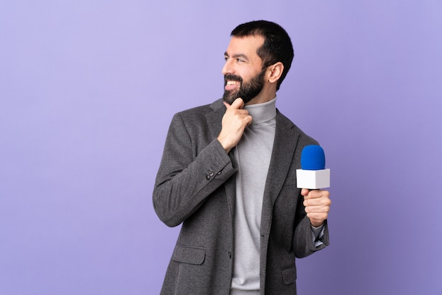 Homme jeune journaliste sur mur isolé