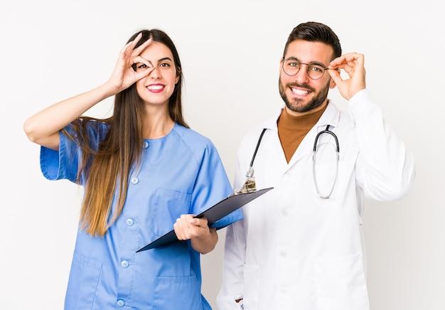 Homme jeune médecin et une infirmière isolée excité en gardant le geste ok sur les yeux.