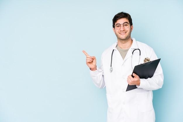 Homme jeune médecin isolé sur un mur bleu souriant et pointant de côté, montrant quelque chose à l'espace vide.