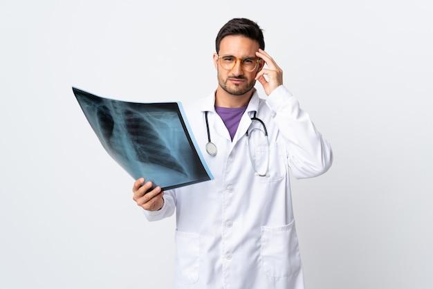 Homme jeune médecin tenant une radiographie isolée sur blanc malheureux et frustré par quelque chose. expression faciale négative
