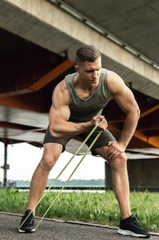 Homme jeune et musclé pendant l'entraînement avec des élastiques de résistance dans une rue. exercice de flexion des biceps.