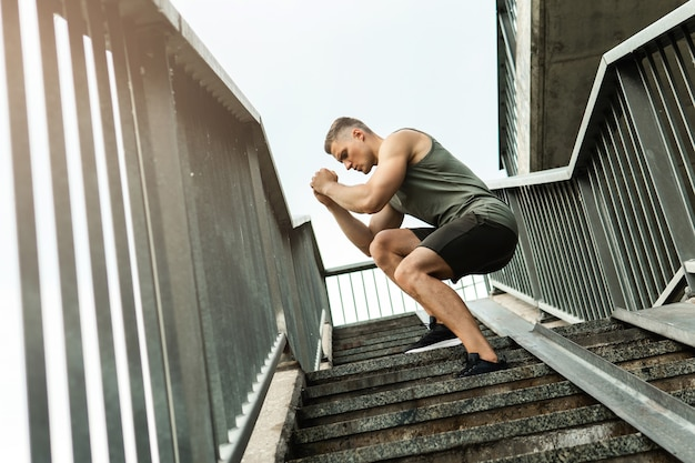 Homme jeune et musclé pendant l'entraînement sur un escalier
