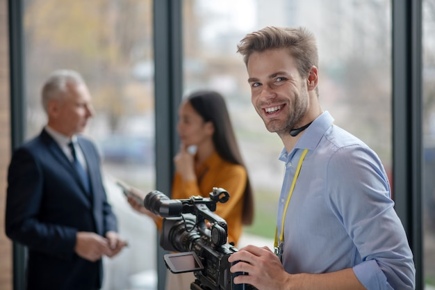 Homme jeune opérateur avec caméra vidéo à la satisfaction de son travail