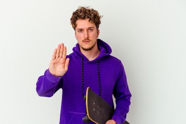 Homme jeune patineur isolé sur mur blanc debout avec la main tendue montrant le panneau d'arrêt, vous empêchant