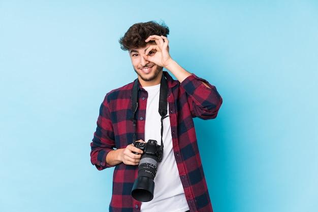 Homme jeune photographe arabe isolé excité en gardant le geste ok sur les yeux.