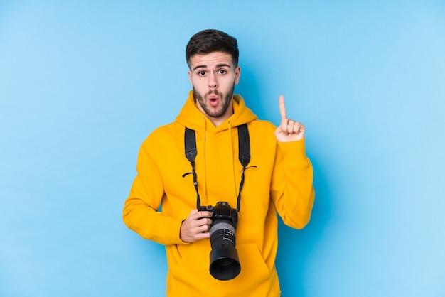 Homme jeune photographe caucasien isolé ayant une excellente idée, concept de créativité.