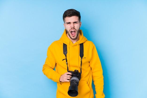 Homme jeune photographe caucasien isolé crier très en colère et agressif.