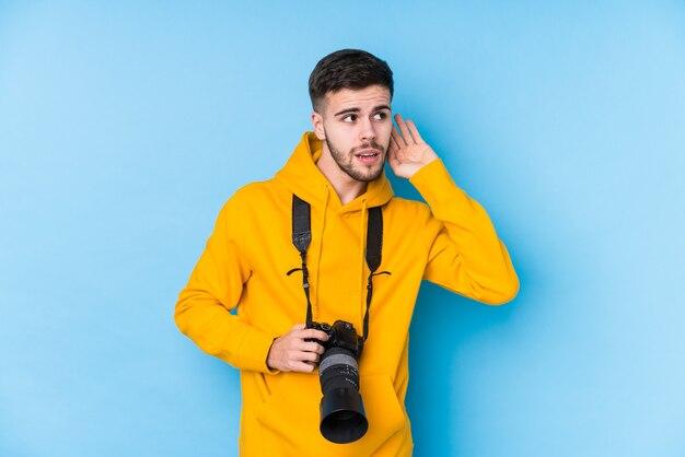 Homme jeune photographe caucasien isolé essayant d'écouter un potin.