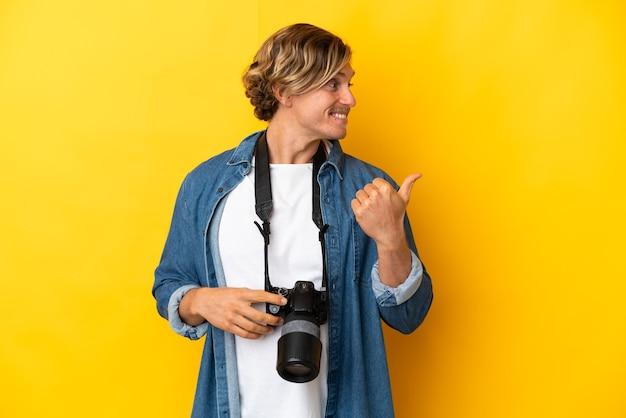 Homme jeune photographe isolé sur fond jaune pointant vers le côté pour présenter un produit